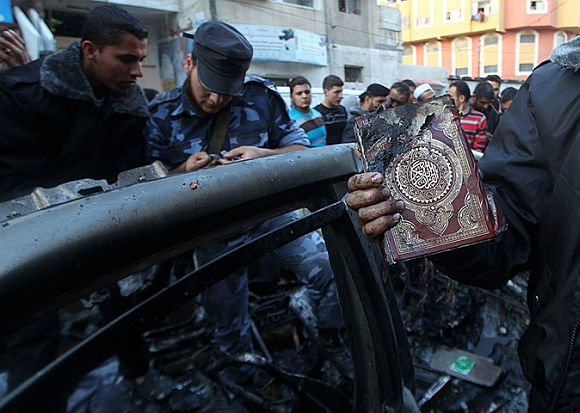 A man holds a damaged copy of the Quran after the Israeli air strike