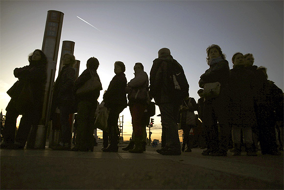 Commuters wait for buses at Atocha rail station during a 24-hour nationwide general strike in Madrid