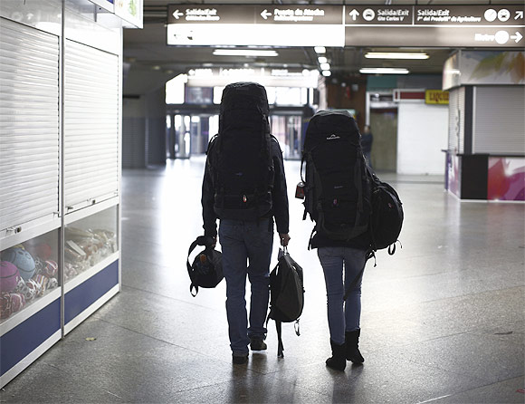 Backpackers walk through a nearly empty terminal at Atocha rail station in Madrid