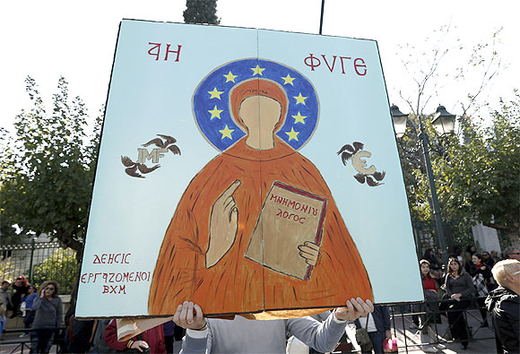 A protester holds a sign with a painting mocking an Orthodox icon during an anti-austerity rally by Greece's public servants unions in Athens