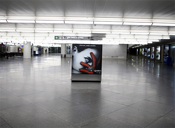 An advertising board is seen at a nearly empty arrival hall at Atocha rail station