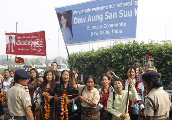 Supporters Suu Kyi, hold banners to welcome her at the Indira Gandhi international airport in New Delhi