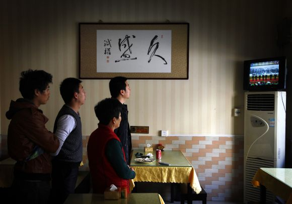 A customer stands with restaurant workers underneath a painting of Chinese characters that reads Long-lasting Prosperity, as they watch television showing the new leadership line-up of China's ruling Communist Party at the Great Hall of the People in Beijing