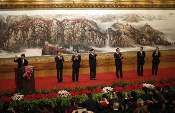 Newly-elected General Secretary of the Central Committee of the Communist Party of China Xi Jinping waves after giving a speech as he meets with the press with other new Politburo Standing Committee members