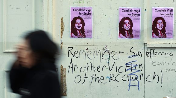A woman walks past posters advertising a candlelit vigil at the University Hospital Galway in Galway, Ireland