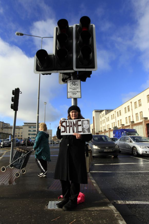Mary Phelan holds a picture of Savita Halappanavar in protest outside University Hospital Galway in Galway, Ireland. Thousands held a candle-lit vigil outside parliament on Wednesday after the news broke of death of Savita Halappanavar, 31, from septicaemia days after miscarrying 17 weeks into her pregnancy and her husband said she had been denied an abortion.