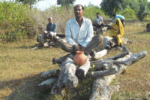 Farmers sit on unlit pyres
