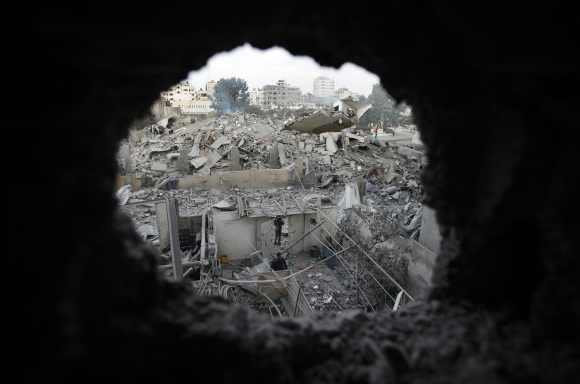 Palestinians are seen through a hole in the wreckage as they inspect the destroyed office building of Hamas Prime Minister Ismail Haniyeh in Gaza City