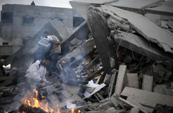 Palestinians inspect the destroyed office building of Hamas Prime Minister Ismail Haniyeh in Gaza City