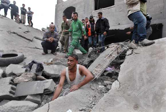 A Palestinian searches for victims under the rubble of the destroyed house of a Hamas official after an Israeli air strike in Jabalya in the northern Gaza Strip