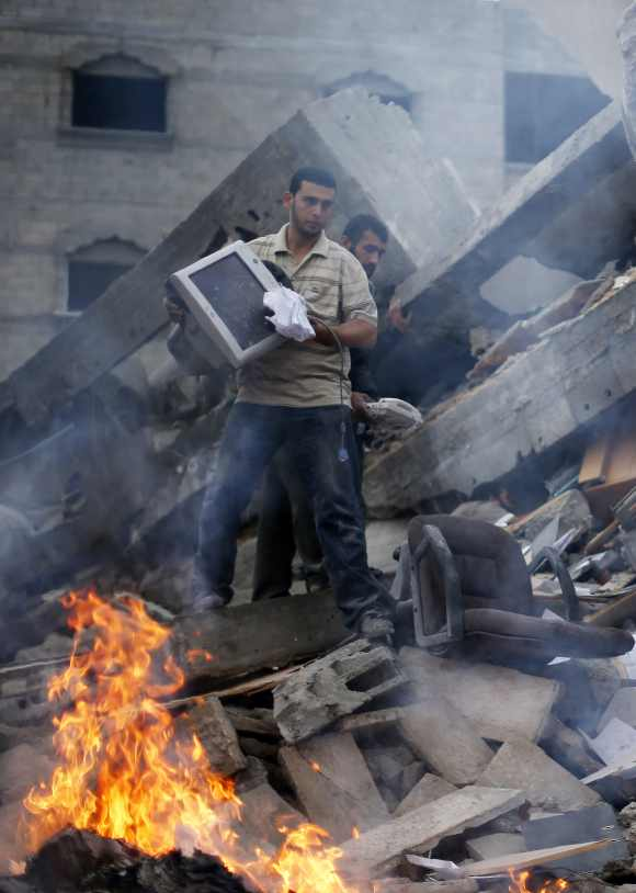 Palestinians remove items from the destroyed office building of Hamas Prime Minister Ismail Haniyeh