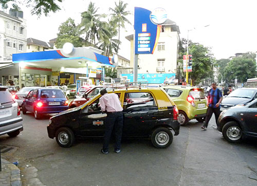 Vehicles pile up at a petrol pump to stock up