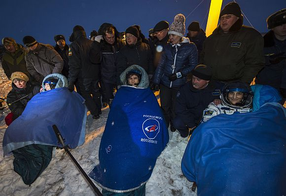 The International Space Station crew members Japanese astronaut Akihiko Hoshide (L), Russian cosmonaut Yuri Malenchenko (C) and US astronaut Sunita Williams rest after landing near the town of Arkalyk in northern Kazakhstan in this NASA handout photograph