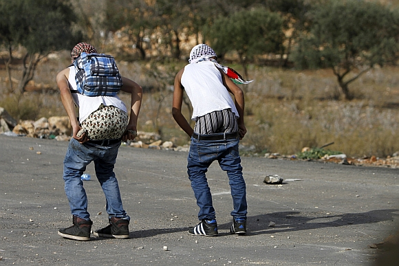 Palestinian stone-throwers pull down their pants in front of Israeli security forces during clashes outside Ofer prison near the West Bank city of Ramallah