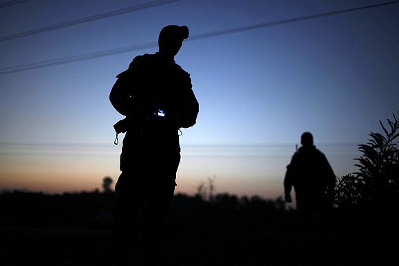 An Israeli soldier stands on the side of the road near the border with the Gaza Strip