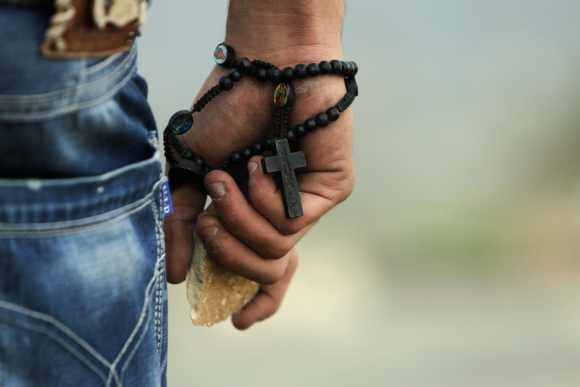 A Palestinian demonstrator wearing a rosary holds a stone during minor clashes with Israeli troops in protest against Israel's military operation in the Gaza Strip, in the West Bank village