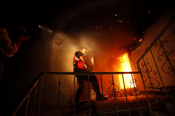 A Palestinian firefighter tries to extinguish a fire after an Israeli air strike, witnessed by a Reuters journalist, on a floor in a building that also houses international media offices in Gaza City
