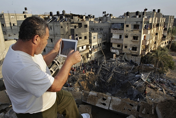 A Palestinian man uses his iPad as he takes pictures of a destroyed house after an Israeli air strike in Khan Younis in the southern Gaza Strip