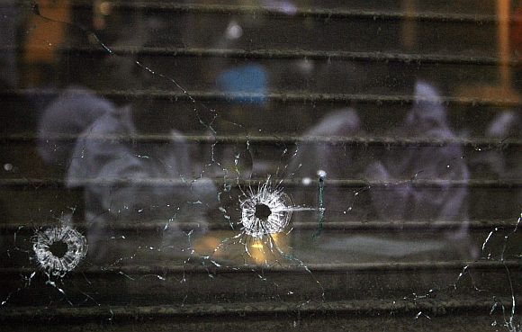 Customers are reflected in a glass pane with bullet holes in Cafe Leopold