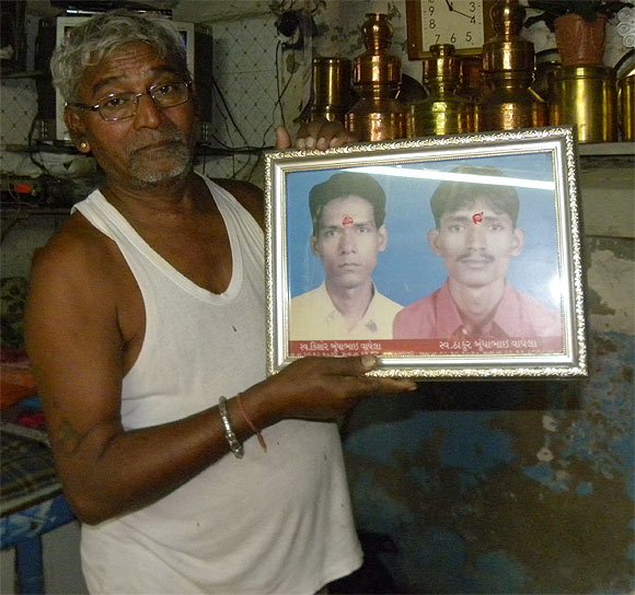 Waghela, with a picture of his sons. Thakur, right, who was killed in the terror attack, while his older son died of an illness in 2004
