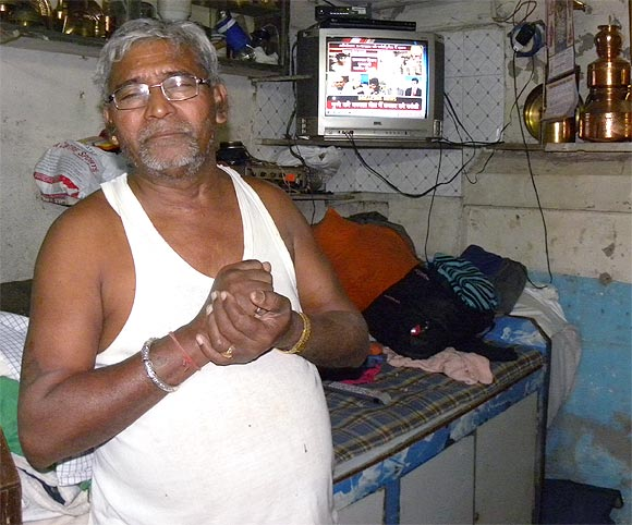 Budhabhai Jethabhai Waghela, who lost his son in 26/11 attacks, watches the news of Kasab's execution