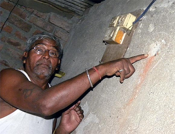 Waghela points to the mark on the wall of his house caused by the bulllet fired by Kasab