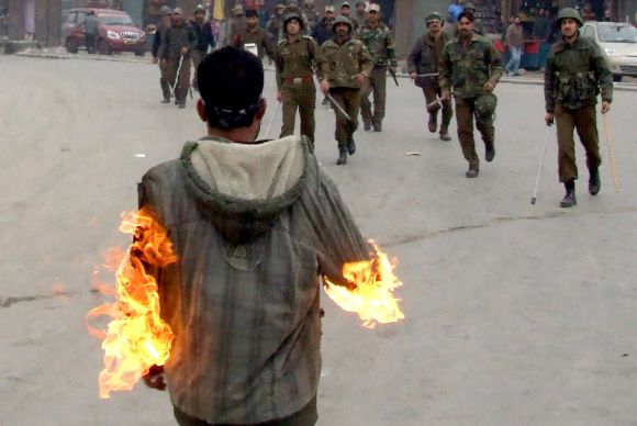 Security personnel rush towards a man who set himself on fire in Srinagar on Friday
