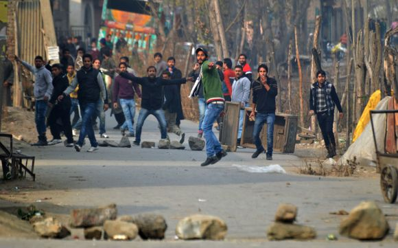A protestor pelts stones towards security personnel during a clash in Srinagar on Friday