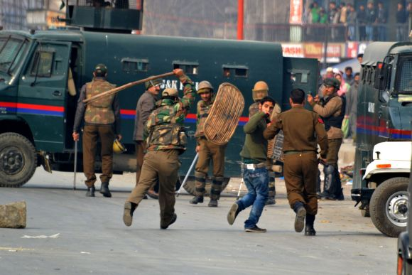 Police personnel lathicharge a protestor in Srinagar on Friday