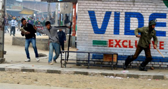 Protestors pelt a stone towards a police personnel in Srinagar on Friday