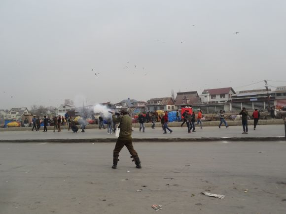 Police fires a tear gas shell to disperse protestors in Srinagar on Friday