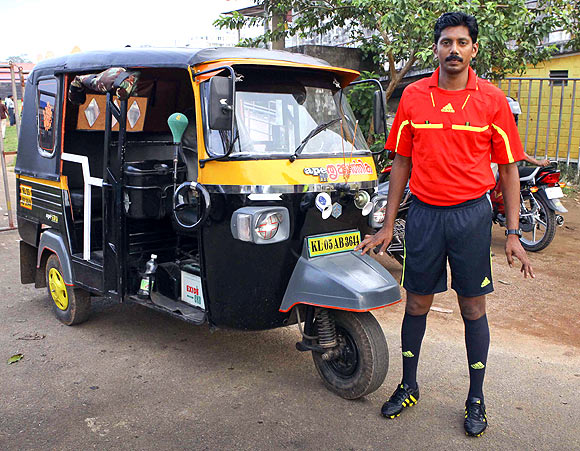 Santhosh Kumar in his referee attire with his autorickshaw