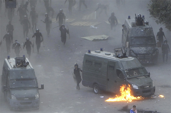Flames burn around a police vehicle after protesters threw a molotov cocktail at it during clashes at Tahrir square