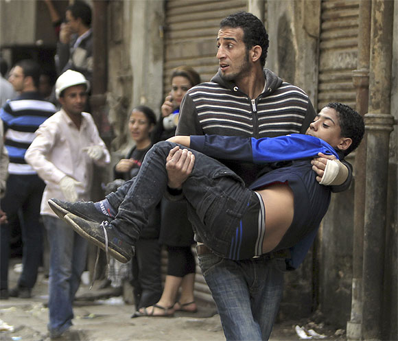 A protester carries an injured fellow protester during clashes with the police at Tahrir square