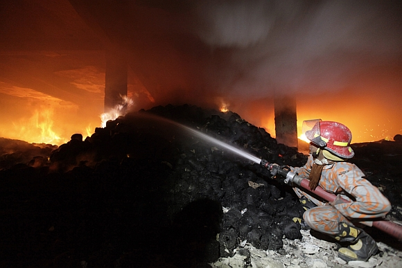 A firefighter tries to control a fire at a garment factory in Savar, outskirts of Dhaka
