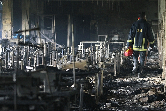 A firefighter inspects a garment factory after a fire in Savar