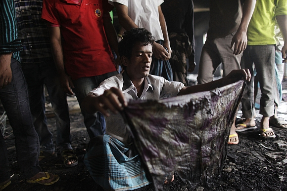 A man shows a piece of cloth which he says belong to his sister-in-law, a missing worker after a devastating fire in a garment factory which killed more than 100 people