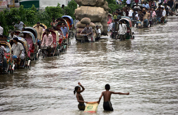 Children play in the flooded water as rickshaw drivers wade down a street in a commercial area in Dhaka