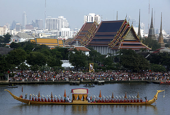 Thai oarsmen row a royal barge on the Chao Phraya River in Bangkok