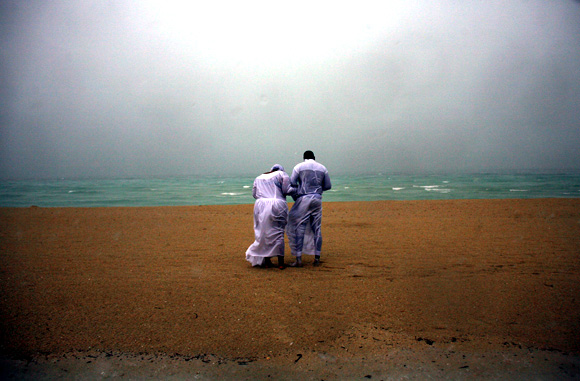 A couple prays at the beach under heavy rain in Miami Beach, Florida