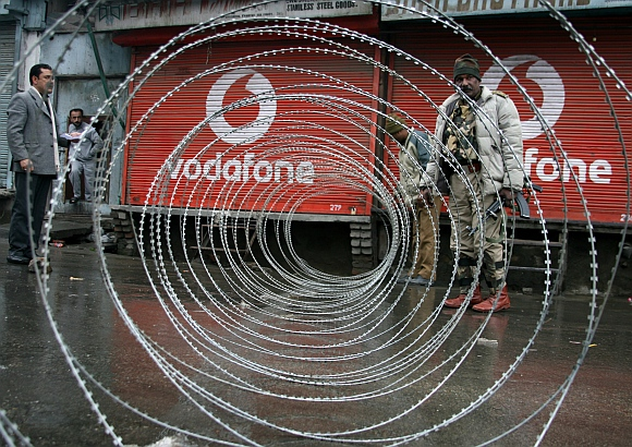 CRPF personnel lay out razor wire to block a road