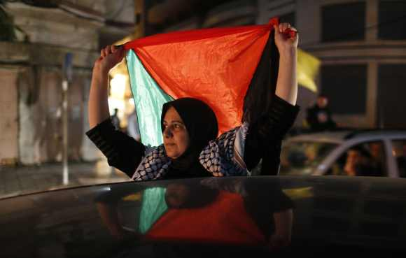 A Palestinian woman holds a Palestinian flag as she celebrates on a street in Gaza City