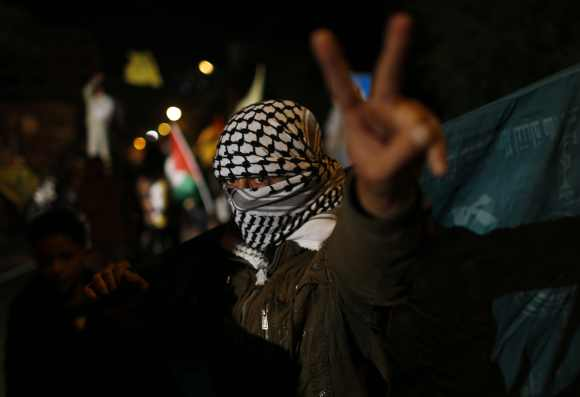 A masked Palestinian gestures as he celebrates on a street in Gaza City on November 30