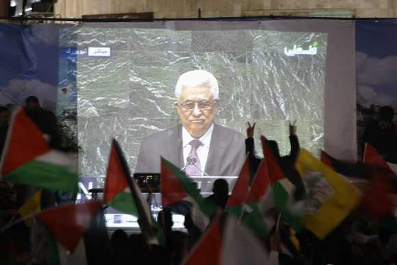 Palestinians take part in a rally while the speech of Palestinian President Mahmoud Abbas is being projected in the West Bank city of Ramallah