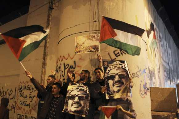 Palestinians hold posters with an image of the late Palestinian leader Yasser Arafat and wave Palestinian flags during a rally opposite to part of Israel's controversial barrier in the West Bank city of Bethlehem