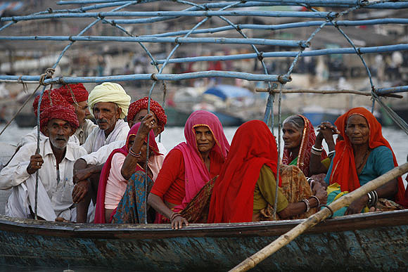 Pilgrims get onto a boat to take a dip in the Sangam