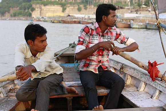 Ashish and Sanjay Nishad row a hired boat and hope to make good business during the Maha Kumbh