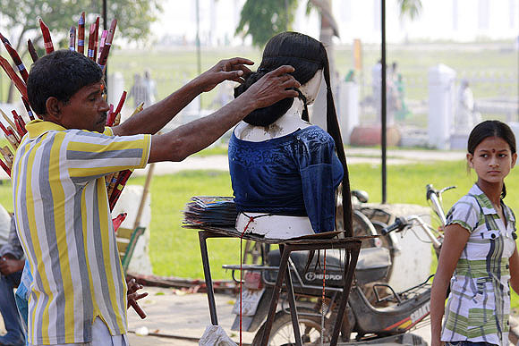 A seller of wigs displays different hairstyles near the ghat