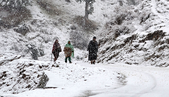 Locals take a walk in heavy snowfall on the Gulmarg-Tangmarg road