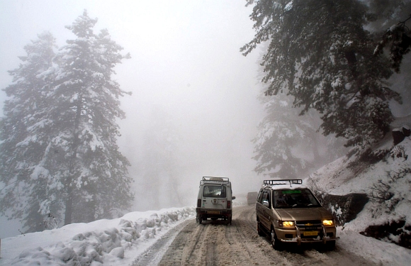 Vehicles pass through snow on the Gulmarg-Tangmarg road
